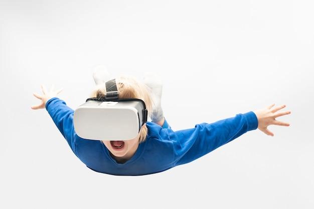 Маленький мальчик в очках виртуальной реальности падает с высоты. белая стена. видеоигры.