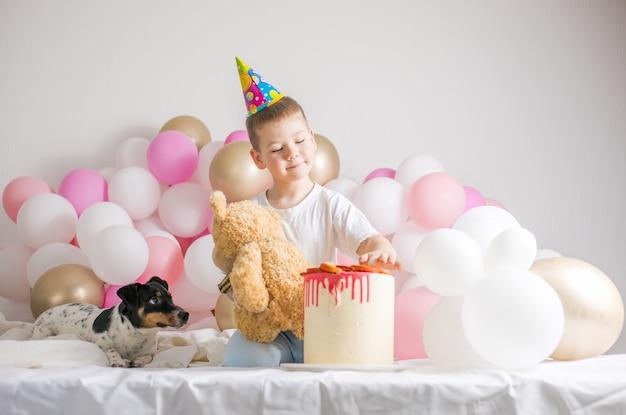 Маленький мальчик в белых шарах с собакой