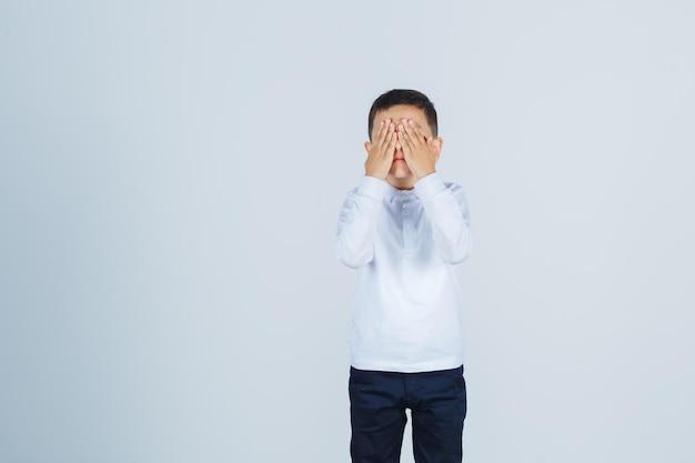 흰 셔츠를 입은 어린 소년, 얼굴에 손을 대고 흥분해 보이는 바지, 전면 전망.
