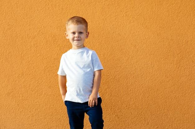 Маленький мальчик в белой футболке. место для вашего логотипа или дизайна. мокап для печати