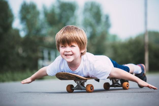 스케이트 보드를 타고 흰색 tshirt에서 어린 소년
