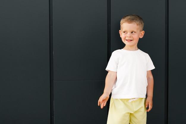 Маленький мальчик в белой футболке с местом для вашего логотипа или дизайнерского макета для печати