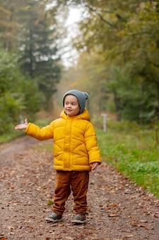 Маленький мальчик в желтой куртке остается в лесу один