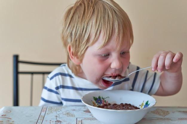 어린 소년이 우유와 함께 초콜릿 공으로 아침 식사를 하고 있습니다. 아이는 우유와 함께 마른 아침 식사를 먹는다