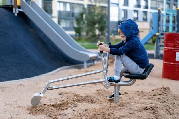 A little boy is having fun playing on the modern urban european playground
