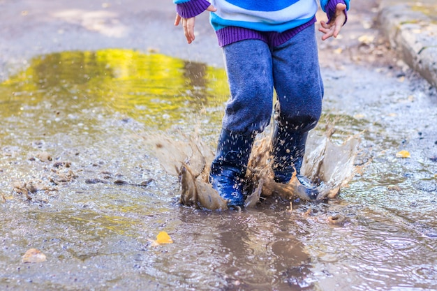 A little boy is jumping in a puddle.
