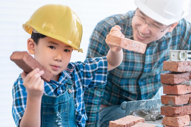 어린 소년은 빈티지 톤으로 그의 건축업자 아버지로부터 벽돌 작업을 내려 놓는 방법을 배우고 있습니다.