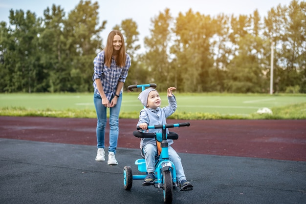 小さな男の子は母親と一緒に歩きながら子供の三輪車に乗ることを学んでいます
