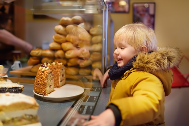 Little boy is looking at christmas sweets in a german bakery