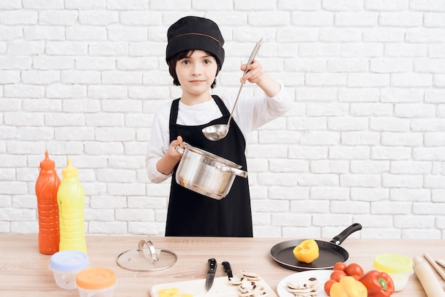The little boy is mastering the profession of cook.