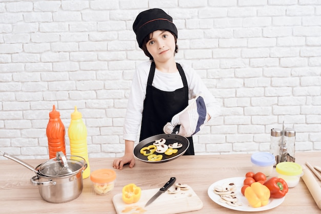 Little boy is mastering the profession of cook.
