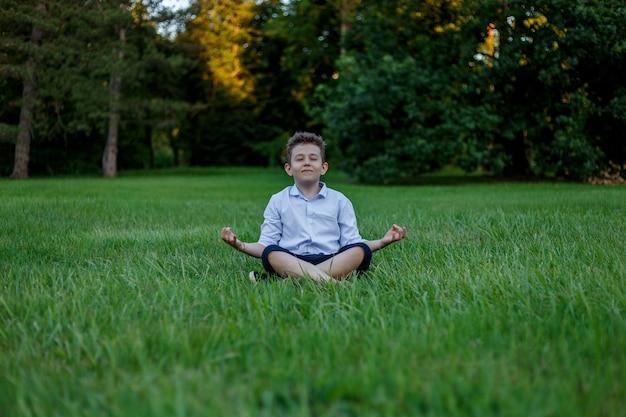 어린 소년은 녹색 초원의 배경에 로터스 위치에서 명상하고 있습니다.
