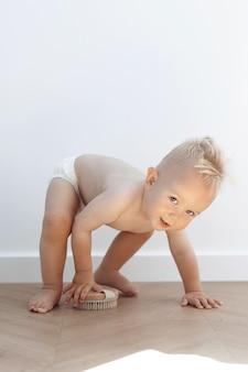 Маленький мальчик играет со стиральной щеткой