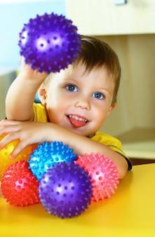 小さな男の子は色のボールで遊んでいます