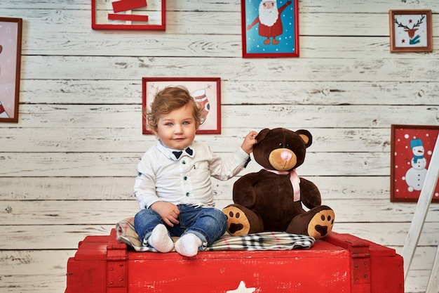 A little boy is sitting on a chest next to a toy.