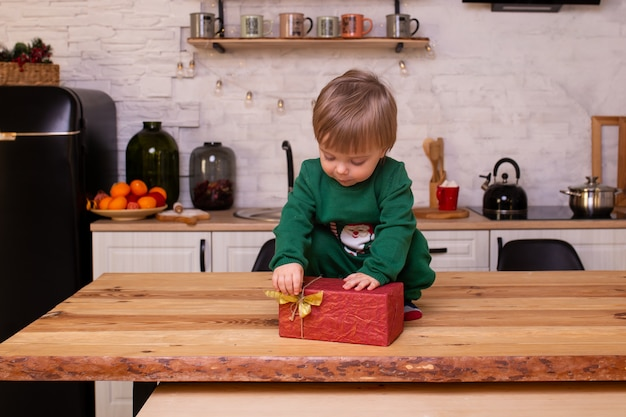 Little boy is sitting on kitchen table.