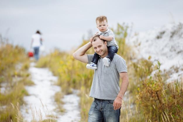Маленький мальчик сидит на плечах отца и играет в парке