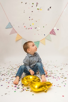 Little boy is sitting in a shirt and trousers and holding a foil gold number two