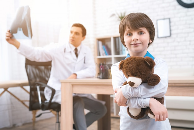 A little boy is standing with a teddy bear in medical room.