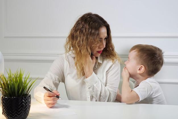 어린 소년은 그녀가 사무실에서 직장에서 전화를 걸고 있는 동안 그녀의 손을 흔들고 웃으면서 일하는 엄마를 멈추고 아들을 엄하게 바라보고 있습니다. 워킹맘.