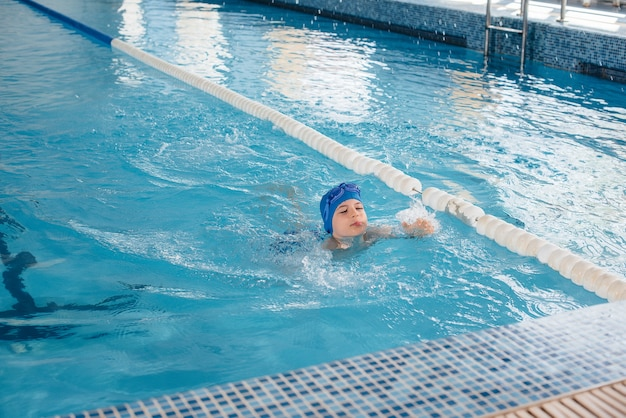 A little boy is swimming and smiling in the pool. healthy lifestyle.
