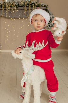 A little boy is waiting for christmas and having fun. the boy is riding a toy deer for christmas