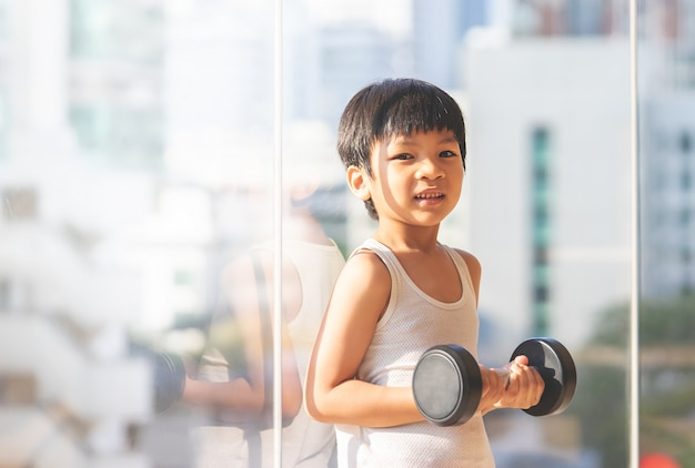 Little boy is working out with dumbbell by the windows city.
