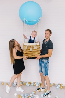 Little boy in jeans on a blue balloon on a white background with his family.
