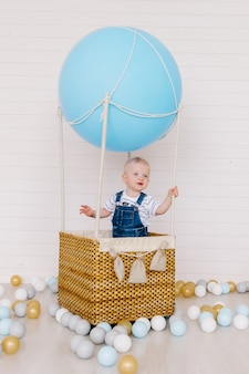 Little boy in jeans on a blue balloon on a white background.