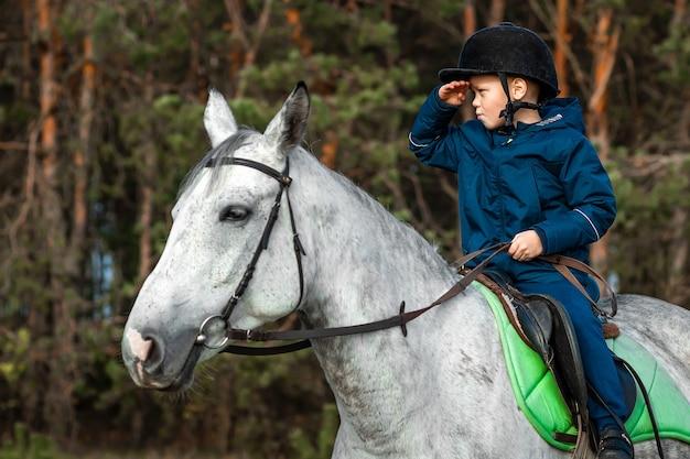 Little boy in a jockey cap on a white adult horse in nature. jockey, hippodrome, horseback riding.