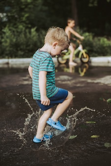Little boy jumping in a puddle in summer