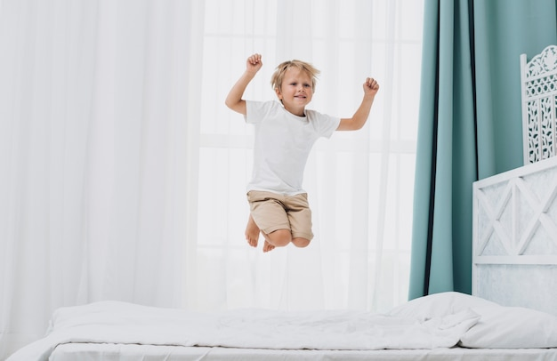 Little boy jumping while looking at the camera