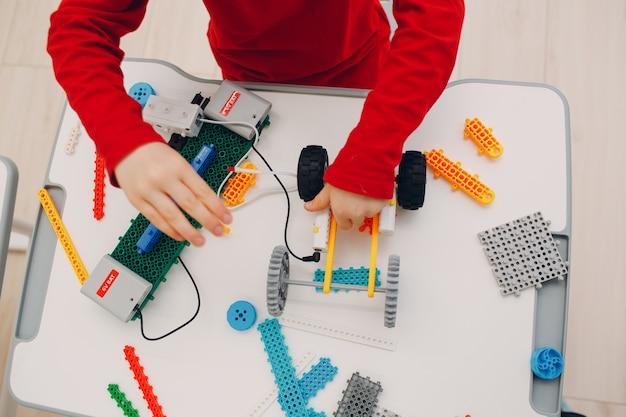 Маленький мальчик ребенок ребенок конструктор проверка технической игрушки детская робототехника конструктор собрать робота