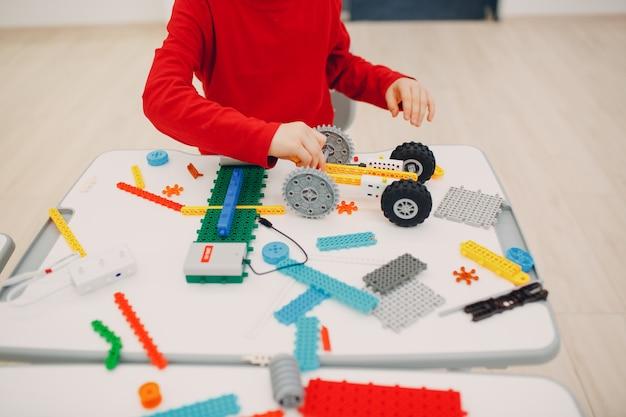 Маленький мальчик ребенок конструктор проверяет техническую игрушку. детский конструктор робототехники собирает робота.
