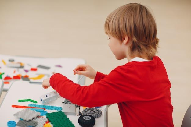 Маленький мальчик ребенок ребенок конструктор проверка технической игрушки детская робототехника конструктор собрать игрушечный робот Premium Фотографии