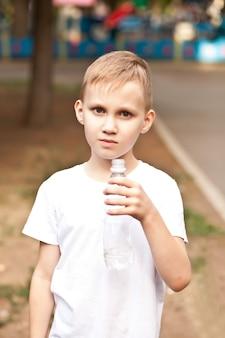 Маленький мальчик ребенок пьет воду из бутылки на открытом воздухе в парке