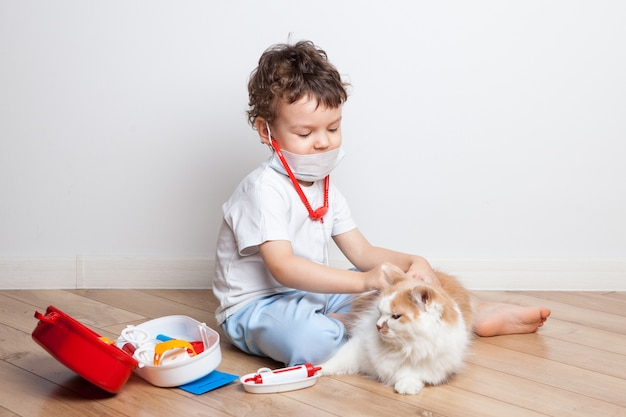 Little boy, kid plays doctor with a cat. first aid kit is lying on the floor with medical first aid tools. a child injects a cat with a toy syringe. friendship with animals.
