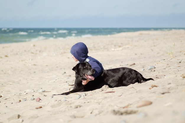 Little boy (kid) with black dog on the seashore, friendship concept