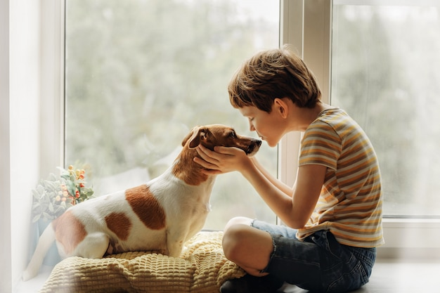 Little boy kisses the dog in nose on the window.