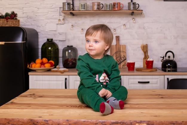 Little boy in kitchen at home is sitting on kitchen table.