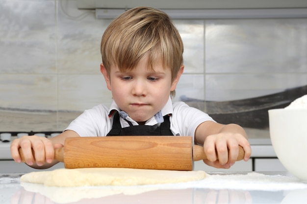 Little boy kneads dough in his hands