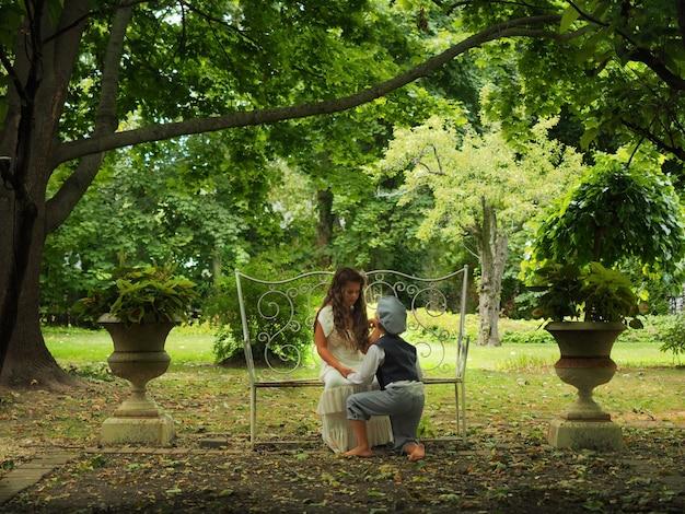 庭で少女の前にひざまずいて少年