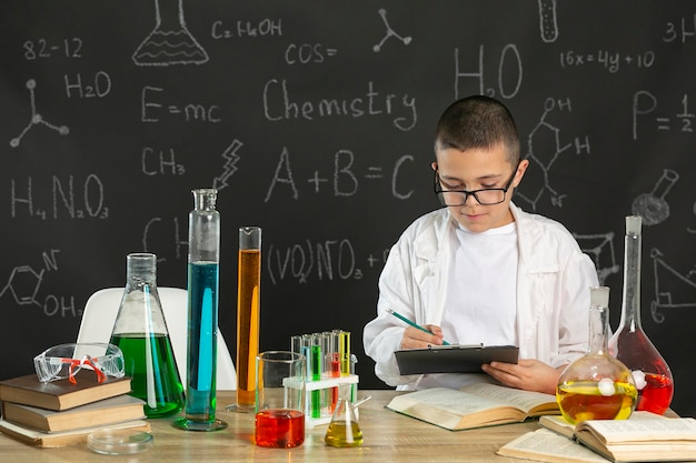Little boy in laboratory with book