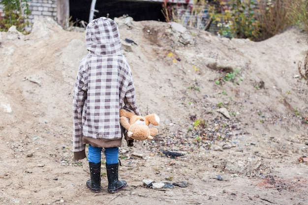 A little boy in larger clothes is standing with a bear in his hands in abandoned places