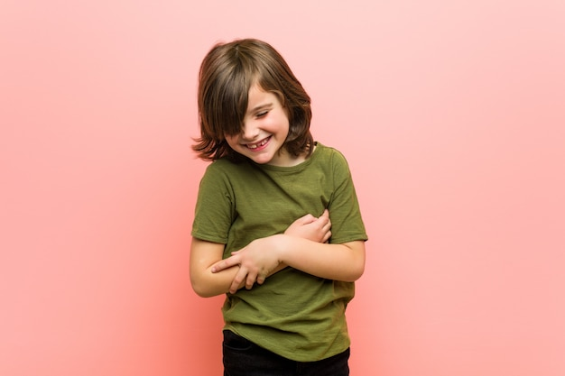 Little boy laughs happily and has fun keeping hands on stomach.