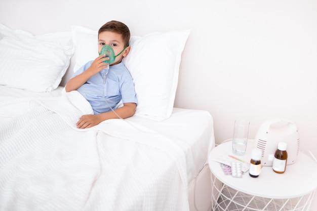 酸素マスクが付いているベッドに敷設の小さな男の子