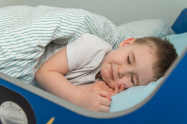 Little boy lays in the bed and pretends he sleep