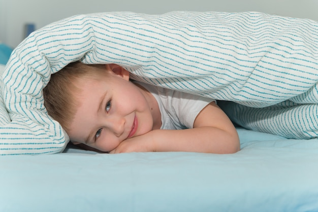 Little boy lays under the blanket and smiling