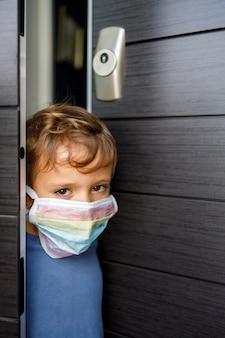무지개의 색으로 그린 마스크와 그의 집의 문을 기대어 어린 소년