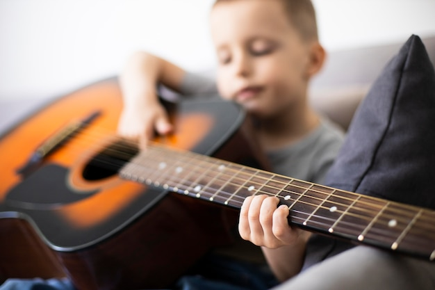 Little boy learning how to play guitar